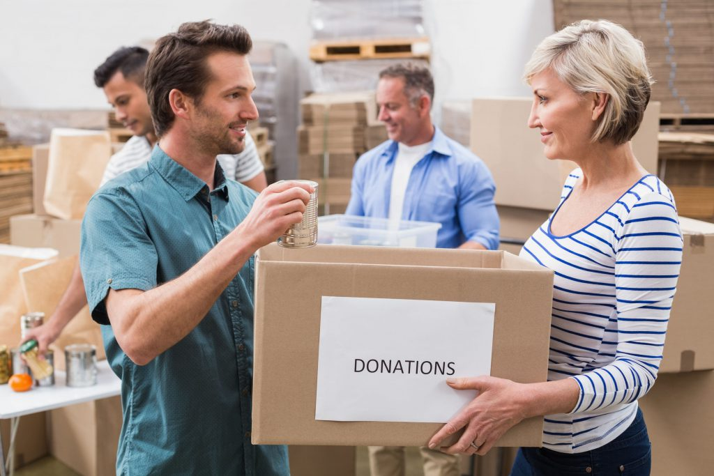 36389579 - two volunteers holding a donations box in a large warehouse